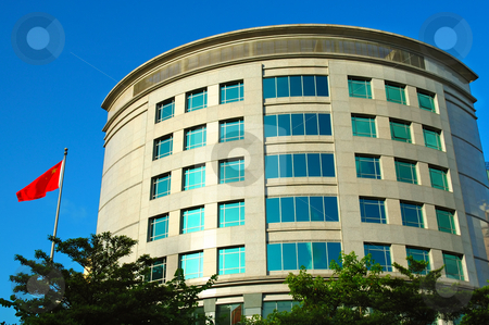 Office building stock photo, Modern office building with a flag over blue sky by Tito Wong