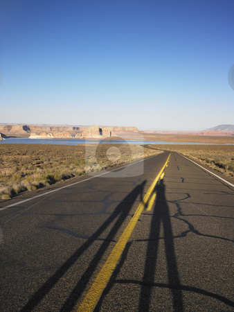 Elongated Shadows of Two People on Road stock photo, Elongated shadows of two people on road. Vertical shot. by Mog Ddl