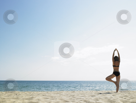 Woman Doing Yoga at the Beach stock photo, Rear view of woman doing yoga at the beach.  Camera looking out towards the water. Horizontal shot. by Mog Ddl