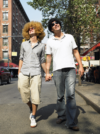 Men In Wigs  stock photo, Men in wigs walking down sidewalk holding hands. Vertical shot. by Mog Ddl
