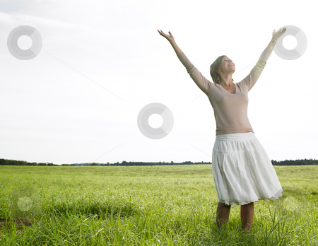 Woman in Field stock photo, Woman in field with arms raised, facing the camera. Horizontal shot. by Mog Ddl