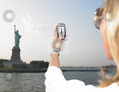 Woman on Vacation in NYC stock photo, Rear view woman using a mobile phone to take a picture of the Statue of Liberty.  Horizontal shot. by Mog Ddl