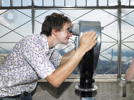 Young Man Looking Through Telescope stock photo, Side view of young man through telescope. Horizontal shot. by Mog Ddl