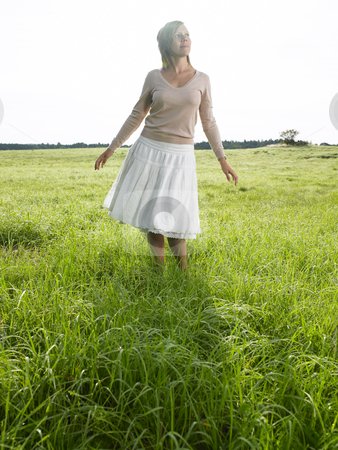 Woman in Field stock photo, Woman in field facing the camera, looking at the sky. Vertical shot. by Mog Ddl