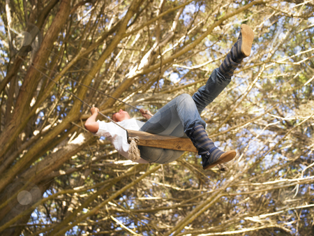 Woman Swinging stock photo, Woman in swing hanging from tree. Horizontal shot. by Mog Ddl