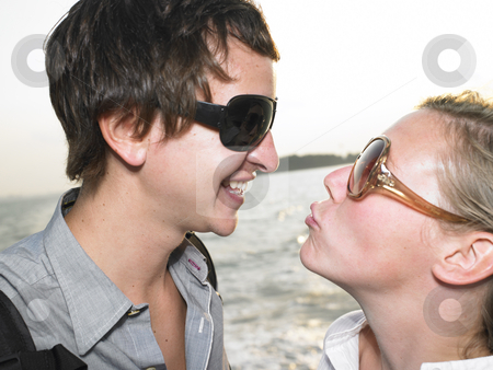 Young Couple on Waterfront stock photo, Young couple about to kiss on the waterfront. Horizontal shot. by Mog Ddl
