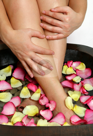Bliss for tired feet stock photo, A woman luxuriates her weary feet with a relaxing footsoak.  Pink and yellow flower petals float on the warm water releasing a heavenly scent. by Leah-Anne Thompson