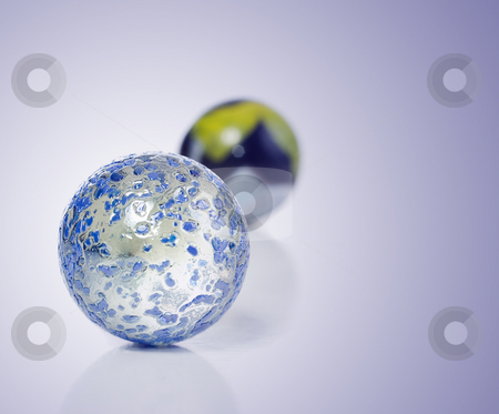 Marbles on Blue stock photo, Closeup view of a game of marbles shot on a white background with a slight reflection on the surface by Richard Nelson