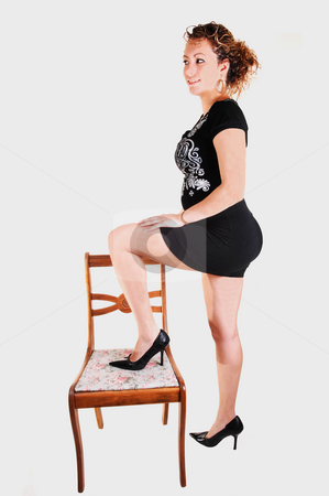 Tall girl in black dress. stock photo, A young pretty woman in an black dress and brunet curly hair standing on a chair for light gray background by Horst Petzold