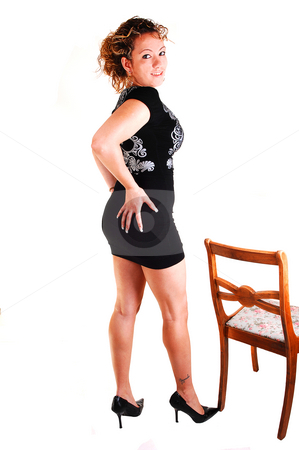 Tall girl in black dress. stock photo, A young pretty woman in an black dress and brunet curly hair standing on a chair for white  background by Horst Petzold