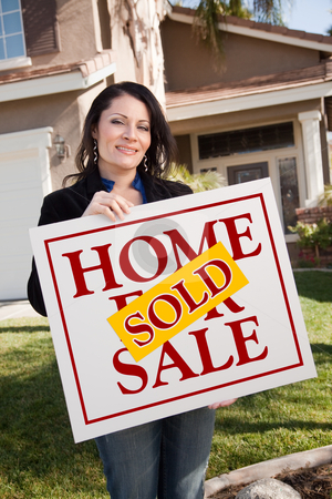 Woman Holding Sold Real Estate Sign In Front of House stock photo, Happy Attractive Hispanic Woman Holding Sold Home For Sale Sign In Front of House. by Andy Dean