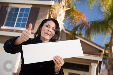 Attractive Hispanic Woman Holding Blank Sign in Front of House stock photo, Happy Attractive Hispanic Woman with Thumbs Up Holding Blank Sign in Front of House. by Andy Dean