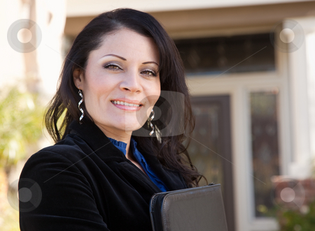 Attractive Hispanic Female Business Woman in Front of New Home stock photo, Proud, Attractive Hispanic Real Estate Agent Woman in Front of New Home. by Andy Dean