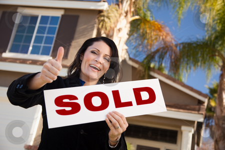 Attractive Hispanic Woman Holding Sold Sign In Front of House stock photo, Happy Attractive Hispanic Woman with Thumbs Up Holding Sold Sign In Front of House. by Andy Dean