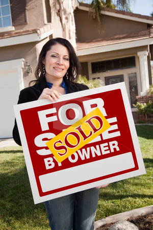 Hispanic Woman Holding Sold For Sale By Owner Real Estate Sign I stock photo, Happy Attractive Hispanic Woman Holding Sold For Sale By Owner Real Estate Sign In Front of House by Andy Dean