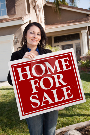 Hispanic Woman Holding Real Estate Sign In Front of House stock photo, Happy Attractive Hispanic Woman Holding Home For Sale Real Estate Sign In Front of House. by Andy Dean