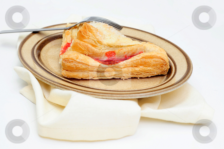 Cherry Turnover Side View stock photo, A sweet Cherry Turnover with course ground sugar on top served on an oval brown colored saucer with a light colored cloth napkin under the plate by Lynn Bendickson