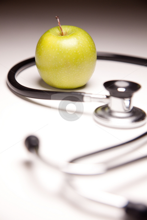 Stethoscope and Green Apple on Gradated Background stock photo, Stethoscope and Green Apple on Gradated Background with Selective Focus. by Andy Dean
