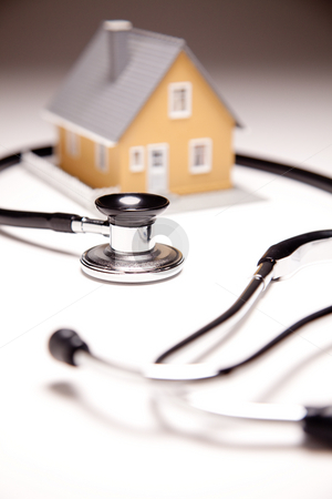 Stethoscope and Model House on Gradated Background stock photo, Stethoscope and Model House on Gradated Background with Selective Focus. by Andy Dean