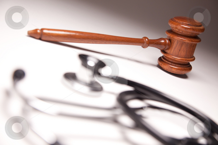 Gavel and Stethoscope on Gradated Background stock photo, Gavel and Stethoscope on Gradated Background with Selective Focus. by Andy Dean