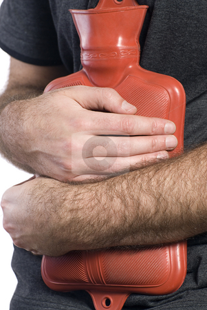 Stomach Flu stock photo, Close-up view of somebody holding a hot water bottle to soothe their sore stomach by Richard Nelson