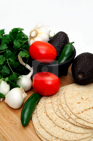 Tomatoes And Tortillas stock photo, Homemade tortilla with fresh natural vegetables including tomato, onion, cilantro, chilies and avocado on a wooden cutting board by Lynn Bendickson