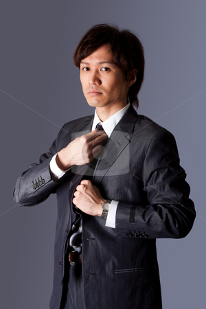 Successful Asian business man fixing tie stock photo, Successful Asian business man standing with confidence and fixing his necktie, isolated. by Paul Hakimata