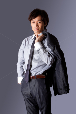 Successful Asian business man  stock photo, Successful Asian business man standing with confidence and jacket over his shoulder and hand in pocket, isolated. by Paul Hakimata