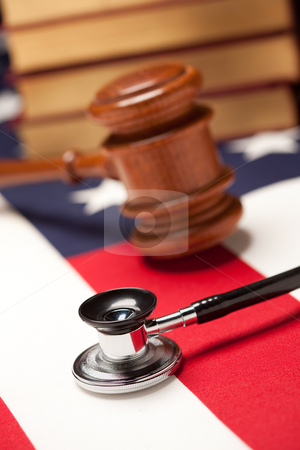Gavel, Stethoscope and Books on Flag stock photo, Gavel, Stethoscope and Books on the American Flag with Selective Focus. by Andy Dean