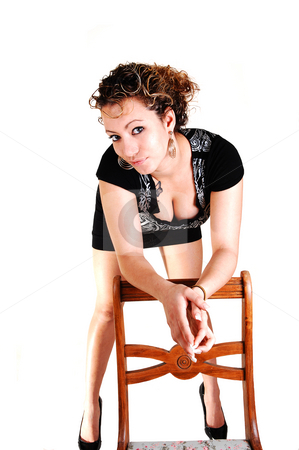Girl in black dress. stock photo, A young pretty woman in an black dress and brunet curly hair standing on a chair for white background by Horst Petzold