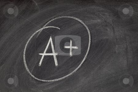 A plus grade on blackboard stock photo, A plus grade handwritten with white chalk on blackboard with eraser smudge texture by Marek Uliasz