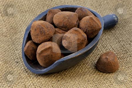 Scoop of chocolate truffles stock photo, Chocolate truffles on a rustic wooden dark painted scoop against burlap background by Marek Uliasz
