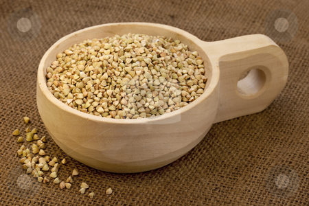 Scoop of buckwheat groats stock photo, Buckwheat groats on a rustic wooden scoop, burlap background by Marek Uliasz
