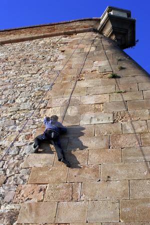 Climber stock photo, A person climbing a stone wall in Montjuic,Barcelona. by Martin Garnham
