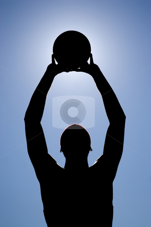 Basketball Player Silhouette stock photo, A silhouette of a young basketball player holding the ball up to the sky. by Todd Arena