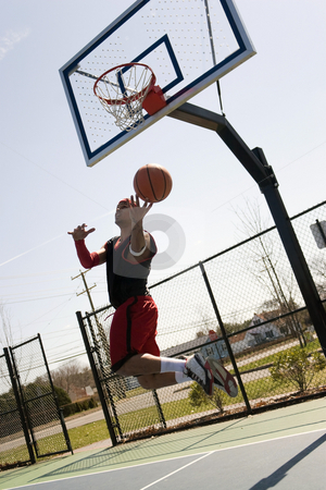 Basketball Player Layup stock photo, A young athlete driving to the basketball hoop for a lay up or slam dunk. by Todd Arena