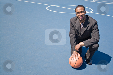 Sports Professional stock photo, A young man in a business suit posing in the empty basketball court with lots of copyspace. by Todd Arena