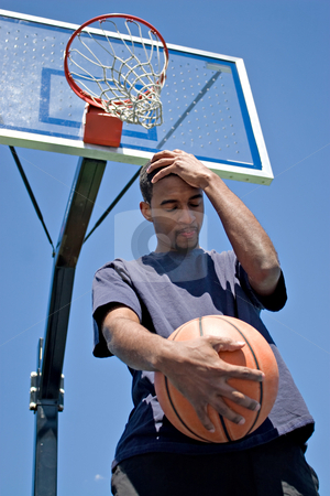 Upset Defeated Athlete stock photo, Basketball player holding his head in disappointment over losing the game. by Todd Arena