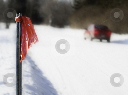 Winter Car Trouble stock photo, A  car having problem on a snowy, windy day.  A red cloth is tied to a pole on the left as a warning to other drivers. by Richard Nelson