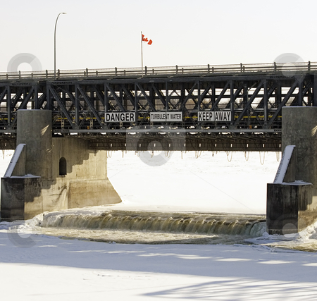 Dangerous Waters stock photo, Close-up view of an open water dam in the winter, with a large sign telling people to stay away because of turbulent water. by Richard Nelson