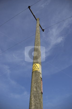 Power line stock photo, Power line with a danger sign and clear blue sky. by Mark Bond