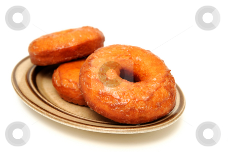 Glazed Donut stock photo, Three homemade glazed donuts on an old fashioned brown oval saucer isolated on a white background by Lynn Bendickson