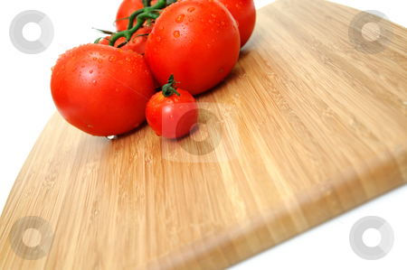 Wet Tomato stock photo, Close-up of large and small tomatoes with water droplets on a wooden cutting board by Lynn Bendickson