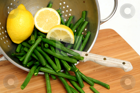 Green Bean stock photo, Green beans with a sliced lemon in a stainless steel colander with a small knife and bamboo cutting board by Lynn Bendickson