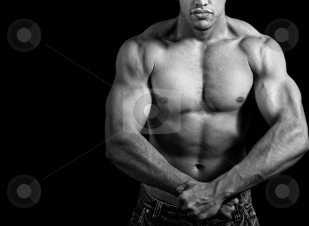 Big athletic man showing his muscles stock photo, Big athletic man showing his muscles over black background by Dunca Daniel