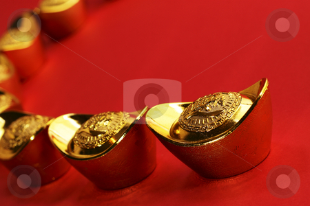 Chinese gold ingots stock photo, A curved row of traditional chinese gold ingots on a red background by Adrin Shamsudin