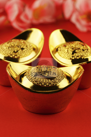 Chinese gold ingots stock photo, A trio of chinese gold ingots on a red background with some cherry blossoms in the background by Adrin Shamsudin