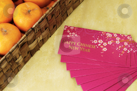 Money packets and oranges stock photo, Chinese New Year money packets with a box of Mandarin Oranges by the side by Adrin Shamsudin