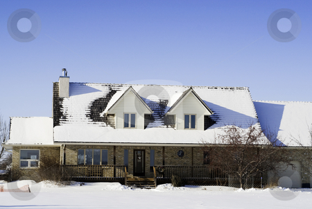 Winter House stock photo, A large house with snow on the roof, shot against a clear blue sky by Richard Nelson