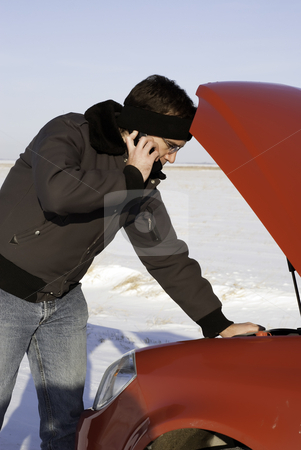 Car Broken Down stock photo, A young man is checking under the car hood while talking on a cell phone. by Richard Nelson